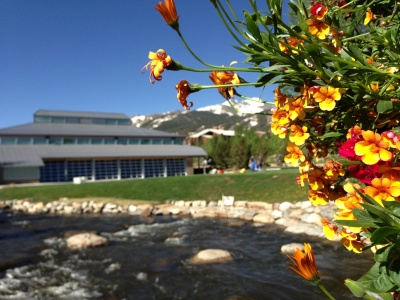 Summer view of the Blue River and Breckenridge Riverwalk Center and events lawn
